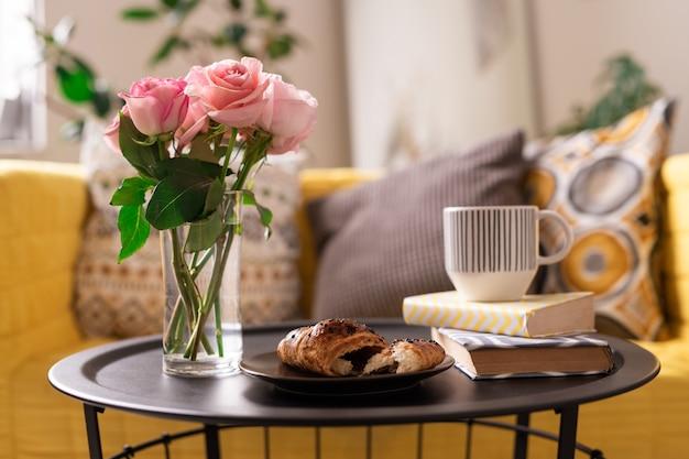 Bos van verse roze rozen in glas water, zelfgemaakte croissant, kopje thee of koffie en twee boeken op dienblad