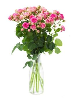 Bos van verse roze rozen in glasvaas die op witte ruimte wordt geïsoleerd