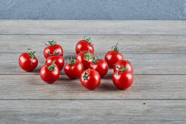 Bos van verse, sappige tomaten op houten tafel.