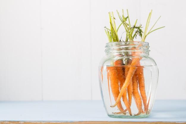 Bos van verse wortelen in glazen vaas met water