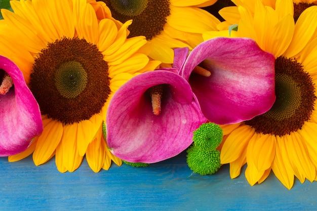 Bos van verse zonnebloemen callas en moeders op blauwe houten achtergrond
