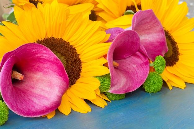 Bos van verse zonnebloemen, roze callas en groene moeders op blauwe achtergrond