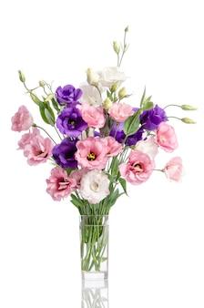 Bos van violette, witte en roze eustomabloemen in glasvaas