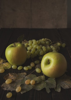 Bos van witte druiven, appels en droge bladeren op het donkere houten oppervlak
