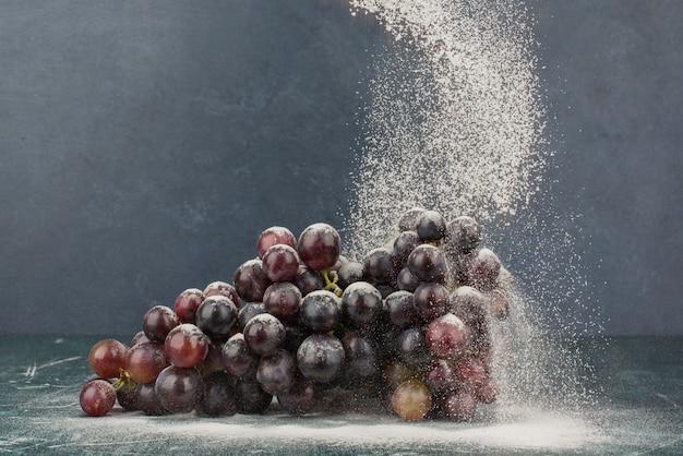 Bos van zwarte druiven versierd met poeder op marmeren tafel