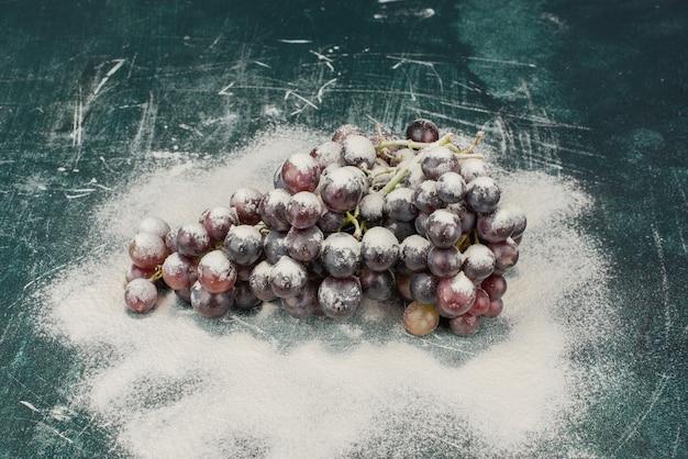 Bos van zwarte druiven versierd met poeder op marmeren tafel.