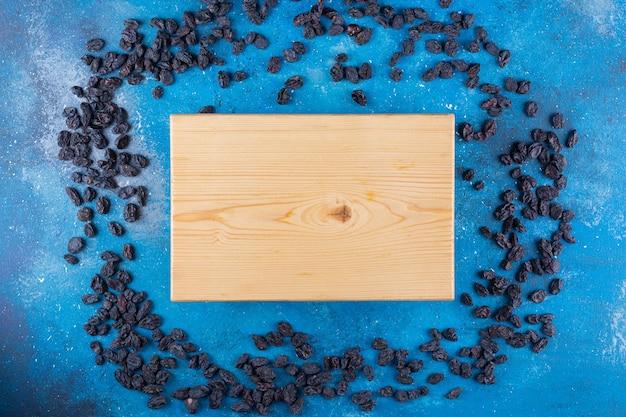 Bos van zwarte rozijnen en houten plank op blauwe tafel.
