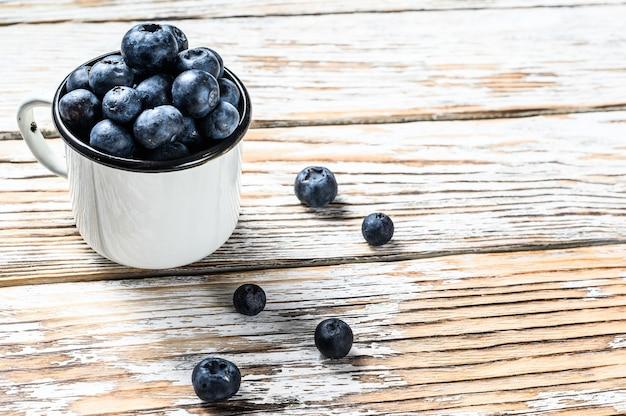 Bosbes in een witte kop. antioxidant biologisch superfood. concept voor gezond eten. witte achtergrond. bovenaanzicht. kopieer ruimte.