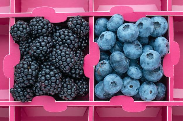 Bosbessen en bramen in een kartonnen doos, roze achtergrond. marktvoedselproduct, bovenaanzicht.