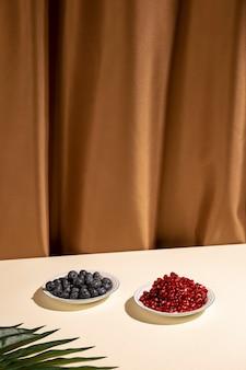 Bosbessen en granaatappelzaden op plaat met palmblad over lijst tegen bruin gordijn