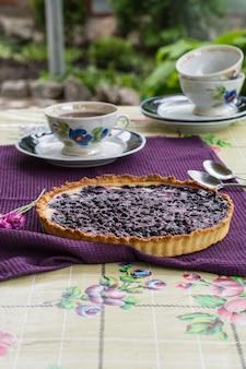 Bosbessen taart. bosbessen taart. buiten ontbijt. theetijd. vintage bekers. kopje thee met Premium Foto