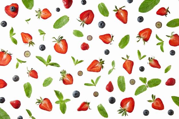 Bosbessenhelften van rijpe aardbeien en groene muntblaadjes