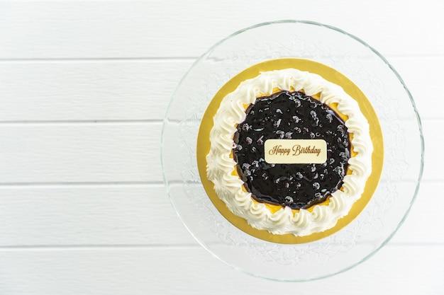 Bosbessenkaastaart met gelukkig verjaardagsteken op bovenkant