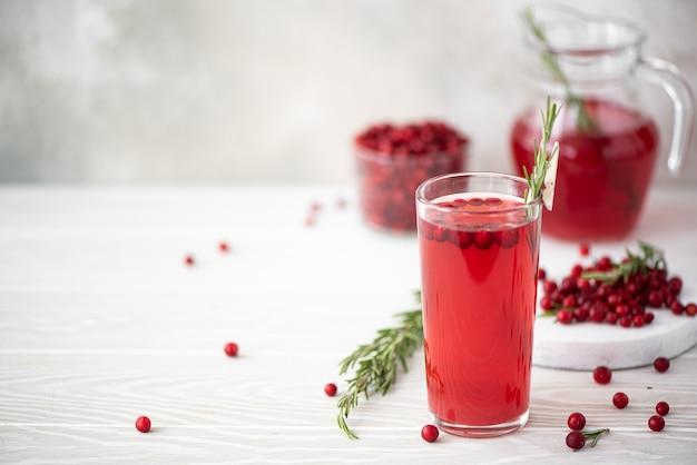 Bosbessensap met rozemarijn en honing in een glazen schaal op een witte tafel