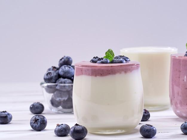 Bosbessenyoghurt en witte yoghurt op houten lijst