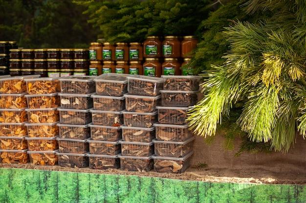 Bosbouw gedroogde paddestoelen in plastic containers op een landelijke kerstmarkt - cantharellen en eekhoorntjesbrood.