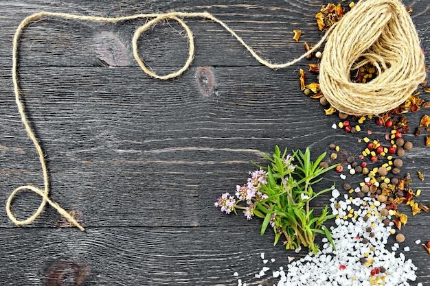 Bosje verse tijm met groene bladeren en roze bloemen, zout, peper, fenegriekzaadjes