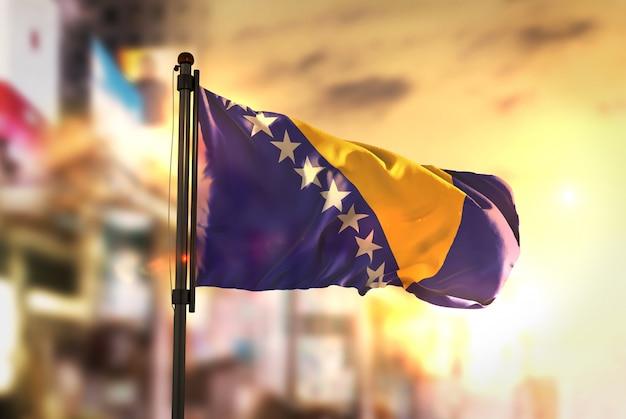 Bosnië-herzegovina vlag tegen stad wazige achtergrond bij zonsopgang achtergrondverlichting