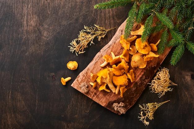 Bospaddestoelen cantharellen en bosmos op een houten oude achtergrond. rauw ongekookt in de kom van de rotanplaat over bruine textuurachtergrond. bespotten. bovenaanzicht.