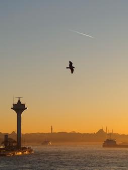 Bosphorusmening bij zonsondergangzeegezicht met vuurtorenzeemeeuw en vliegtuigspoor