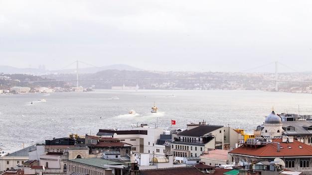 Bosporus met daarin drijvende schepen en een brug over het water, mist, bewolkt weer in istanbul