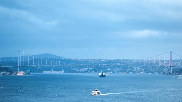 Bosporus met daarin drijvende schepen en een verlichte brug over het water, mist, bewolkt weer, istanboel, turkije