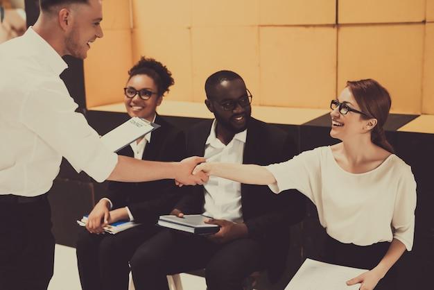 Boss shakes medewerkers hand op zakelijke bijeenkomst.