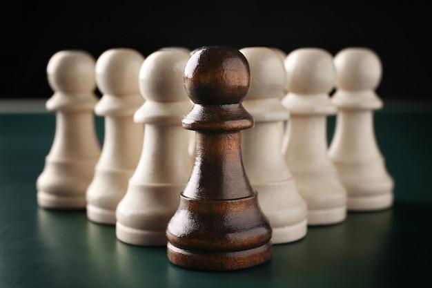 Boss vs leader-concept. schaakstukken op donkere achtergrond