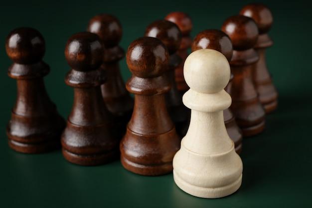 Boss vs leader-concept. schaakstukken op groene achtergrond