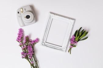 Bossen van bloemen dichtbij fotolijst en camera