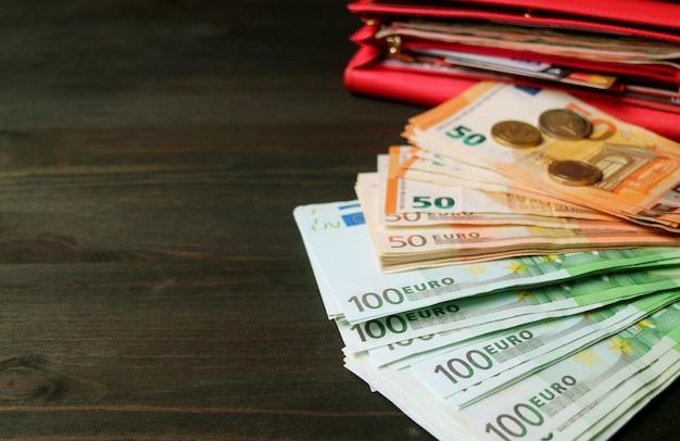 Bossen van eurobankbiljetten met wazige munten en een rode portemonnee openen