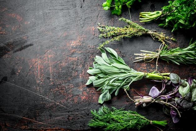 Bossen van verse kruiden voor de salade op zwarte rustieke tafel