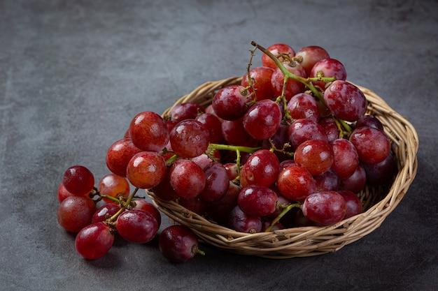 Bossen van verse rijpe rode druiven op het donkere oppervlak.