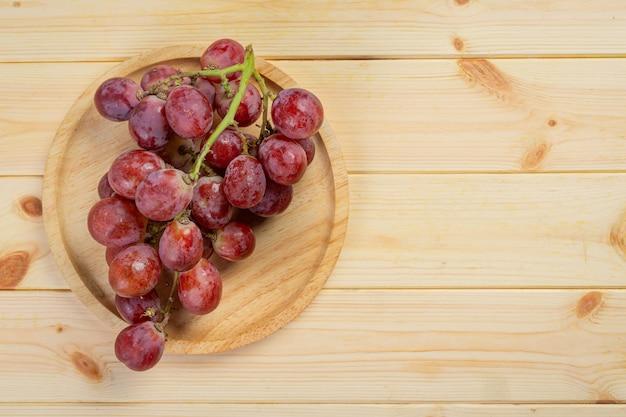 Bossen van verse rijpe rode druiven op het houten oppervlak.