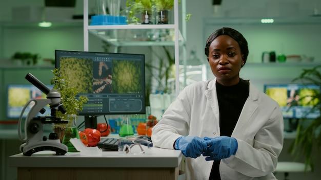 Botanicus-onderzoekervrouw legt botanie-experiment uit tijdens online videogesprekvergadering terwijl ze in een farmaceutisch laboratorium zit