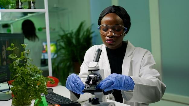 Botanische vrouw kijkt naar testmonster onder de microscoop en observeert genetische mutatie op planten