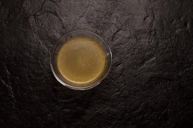 Botbouillon met natuurlijk collageen in glas op een donkere stenen ondergrond.