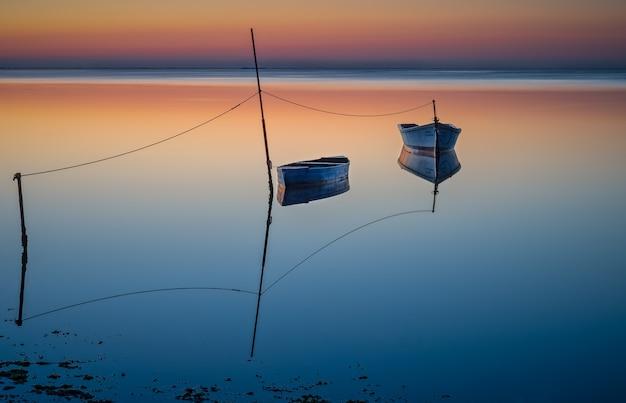 Boten drijven ob het water onder de kleurrijke hemel