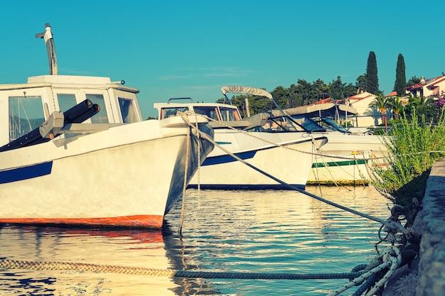 Boten en huizen in vrboska-dorp, hvar-eiland, dalmatië, kroatië, europa. afgezwakt zomerzeetransport.