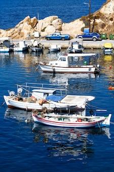 Boten in de haven van nea roda op blauw zeewater, halkidiki, griekenland
