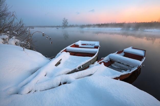 Boten in sneeuw bij de rivier in de winter