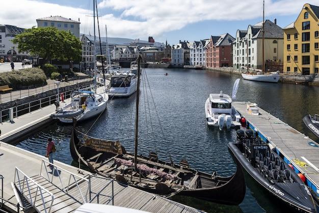 Boten op een brede waterkanaal omgeven door kleurrijke gebouwen in alesund, noorwegen