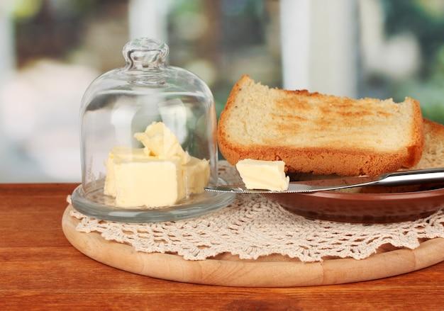 Boter op glazen schotel met glazen deksel omgeven door brood, op lichte achtergrond