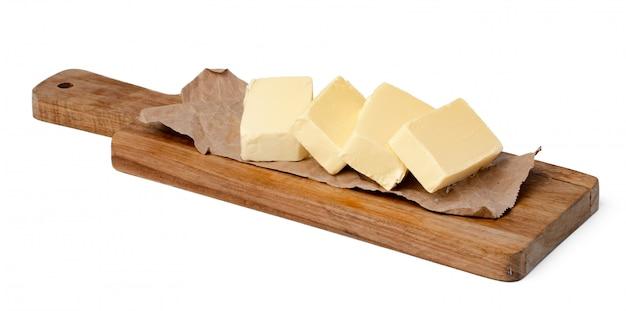 Boter op houten raad die op witte achtergrond wordt geïsoleerd