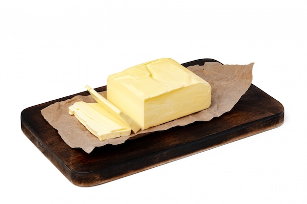 Boter op houten raad die op witte muur wordt geïsoleerd
