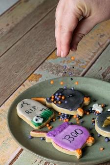 Boterachtige koekjes met halloween-thema worden versierd door een banketbakker met suikerballen.