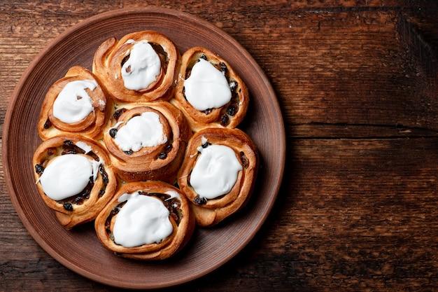 Boterachtige zoete broodjes met rozijnen op een bruine houten ondergrond. afgedekt met witte suikersiroop. plaats voor tekst.