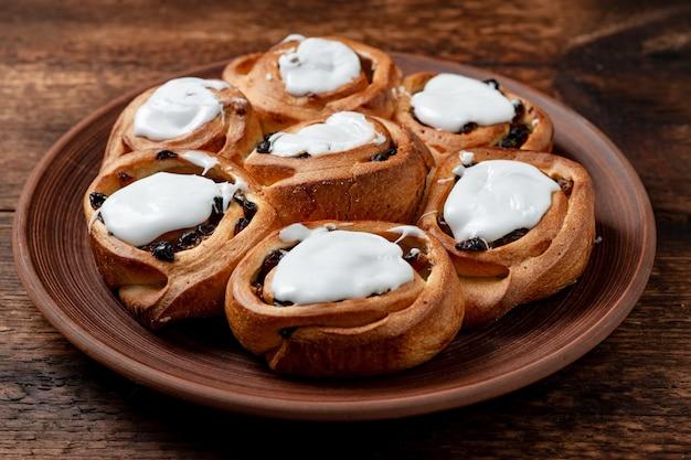 Boterachtige zoete broodjes met rozijnen op een bruine kleiplaat. afgedekt met witte suikersiroop.