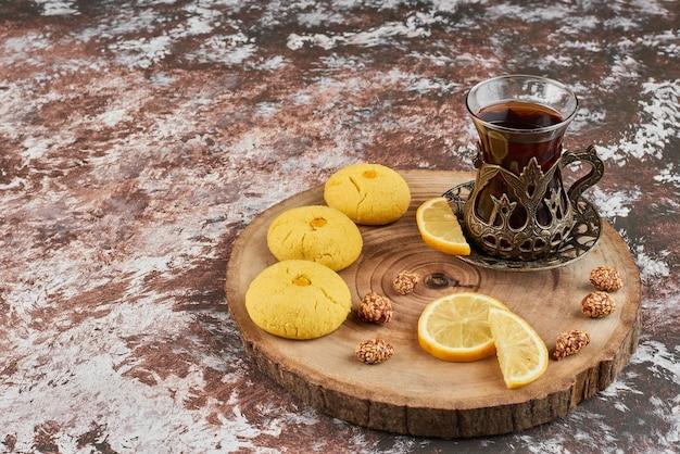 Boterkoekjes en een glas thee op een houten bord.