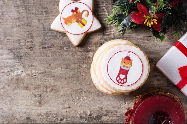 Boterkoekjes van kerstmis die met kerstmisgrafiek worden verfraaid, op houten lijst copyspace